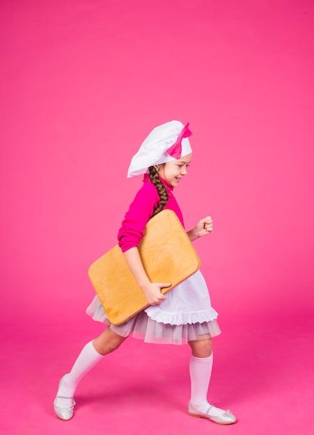Linda garota cozinhar vai com placa de madeira Foto gratuita