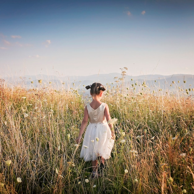 Linda garota dançando através de um belo prado com trigo e flores nas montanhas, vista traseira Foto Premium
