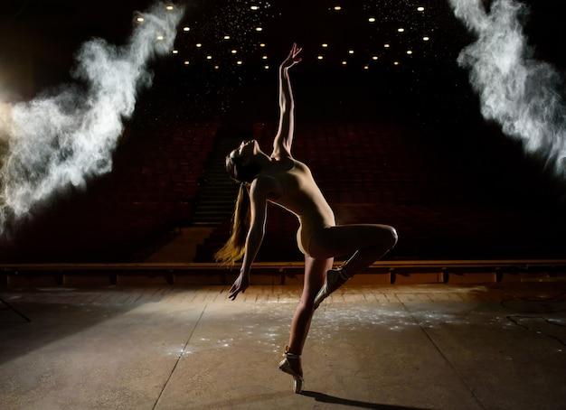 Linda garota dançando em um fundo preto. Foto Premium