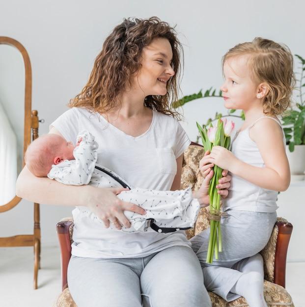 Linda garota dando flores tulipa para a mãe dela segurando bebê sentado na cadeira de braço Foto gratuita
