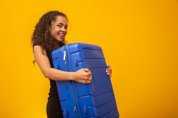 Linda garota de cabelos crespos na mala de viagem. próxima viagem Foto Premium