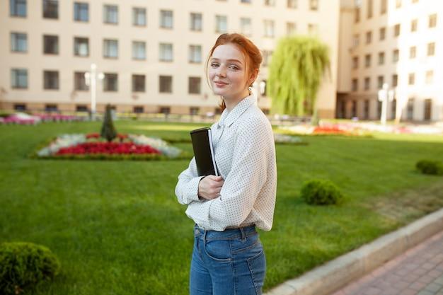 Linda garota de cabelos vermelha com sardas abraçando cadernos Foto Premium