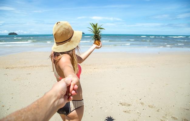 Linda garota de maiô e abacaxi caminha na praia segurando a mão do cara Foto gratuita