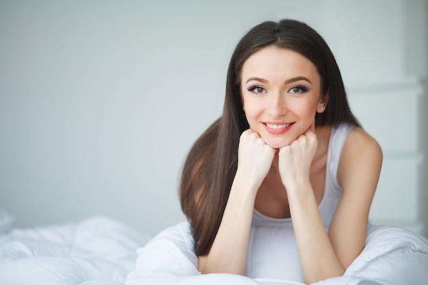 Linda garota de manhã em uma cama branca Foto Premium