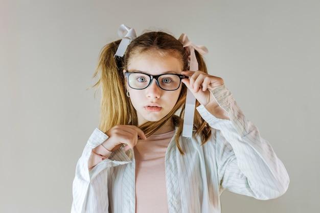 Linda garota de óculos segurando o cabelo dela Foto gratuita