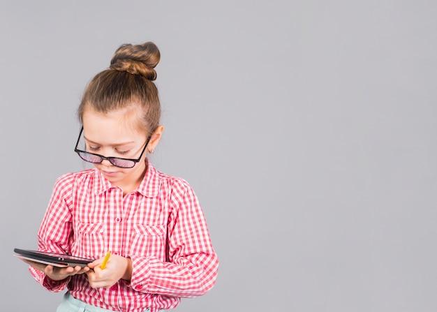Linda garota de óculos usando tablet Foto gratuita
