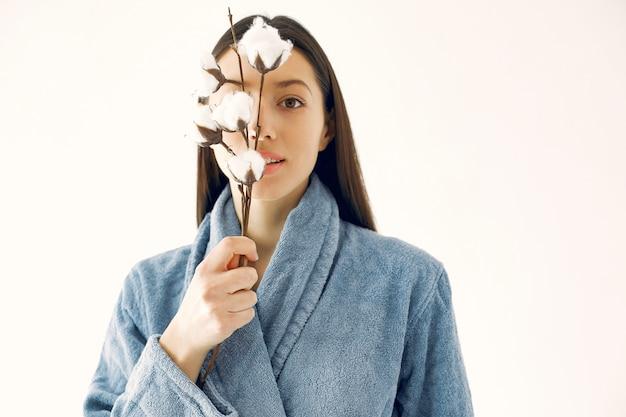 Linda garota de pé em um estúdio com flores de algodão Foto gratuita