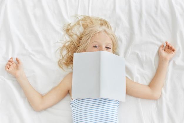 Linda garota de pijama, lendo contos de fadas na cama, cobrindo o rosto com o livro. Foto gratuita