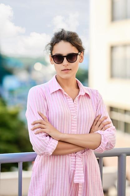 Linda garota de vestido listrado vermelho e óculos de sol em pé na varanda Foto Premium