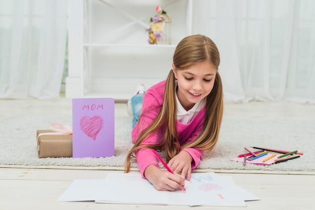 Linda garota, desenho em papel perto de cartão Foto gratuita