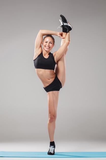 Linda garota desportiva em pé em pose de acrobata Foto gratuita