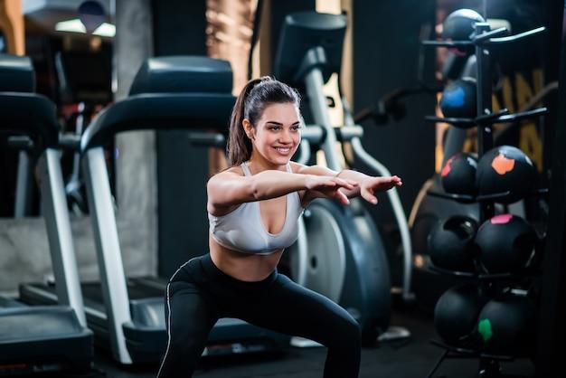 Linda garota desportiva fazendo agachamentos no ginásio. Foto Premium
