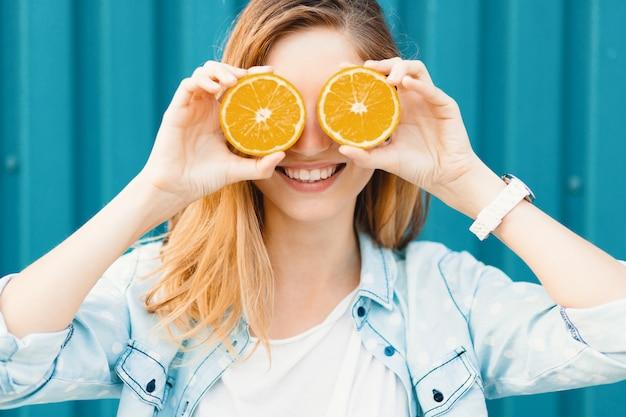 Linda garota despreocupada usando duas metades de laranjas em vez de óculos sobre os olhos Foto gratuita