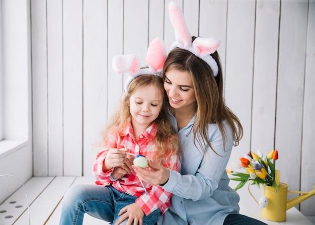 Linda garota e mãe em orelhas de coelho pintando ovos para a páscoa Foto gratuita