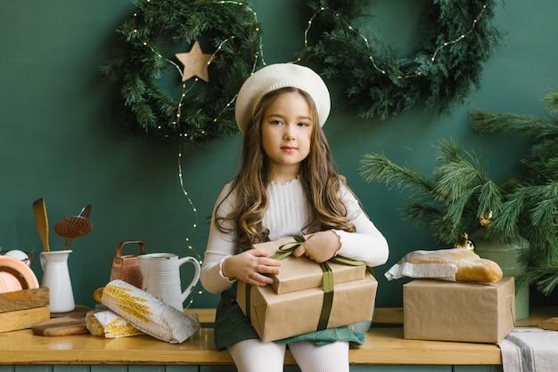 Linda garota elegante em uma boina branca segurando os presentes de natal e sentado na cozinha cor de esmeralda, decorada para o feriado do ano novo Foto Premium