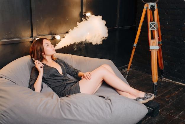 Linda garota elegante fumando um cigarro eletrônico - dispositivo moderno, livre de tabaco, exalando vapor durante o repouso e o relaxamento no pufe cinza no quarto escuro e velho. interior Foto Premium