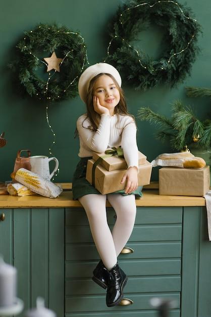 Linda garota elegante na cozinha decorada para o natal e ano novo. ela está segurando caixas de presente Foto Premium