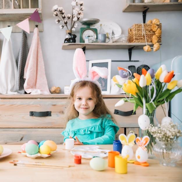 Linda garota em orelhas de coelho sentado à mesa com ovos coloridos Foto gratuita