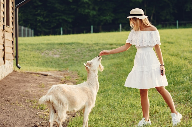 Linda garota em um campo com uma cabras Foto gratuita