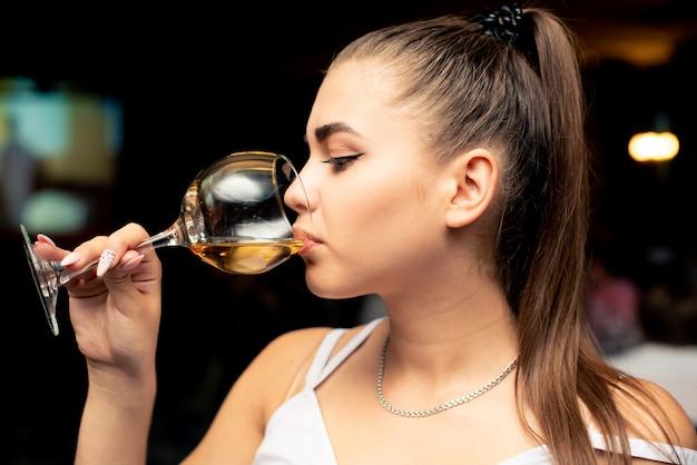 Linda garota em uma blusa branca está bebendo vinho com um copo Foto Premium