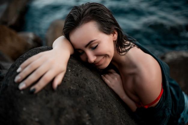 Linda garota em uma camisa preta e um sutiã vermelho está deitado sobre uma pedra Foto Premium