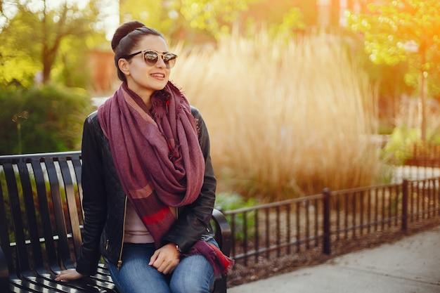 Linda garota em uma jaqueta de couro e cachecol sentado nas ruas de chicago Foto gratuita