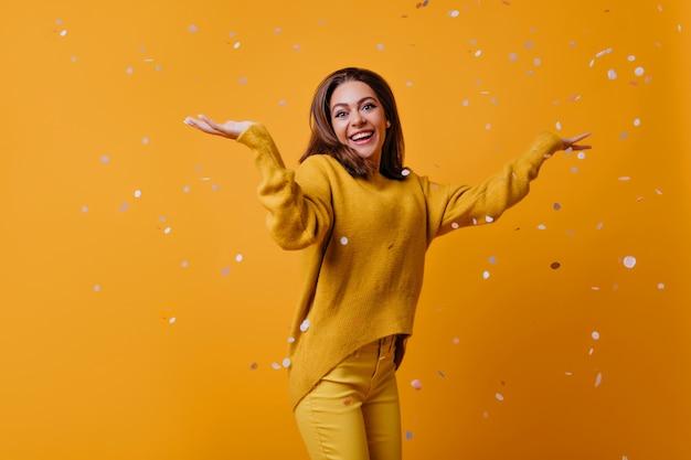 Linda garota espantada com cabelo escuro dançando na parede amarela. atraente e elegante mulher jogando confete. Foto gratuita