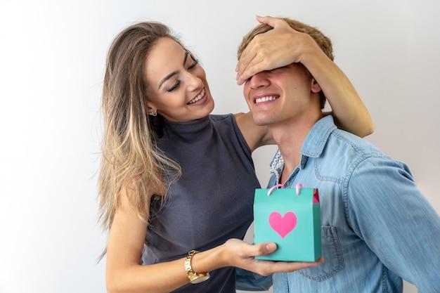 Linda garota está cobrindo os olhos do namorado dela e dando-lhe um presente, em fundo cinza Foto Premium
