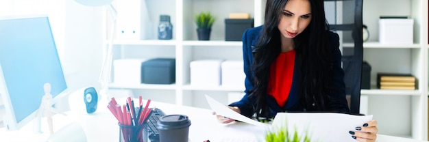 Linda garota está olhando através de documentos, sentado no escritório à mesa. Foto Premium