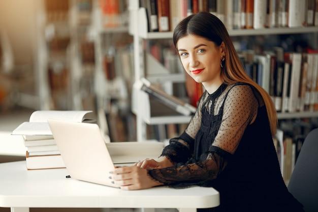 Linda garota estudar na biblioteca Foto gratuita