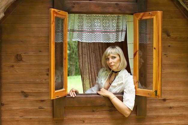Linda garota européia olha pela janela Foto Premium