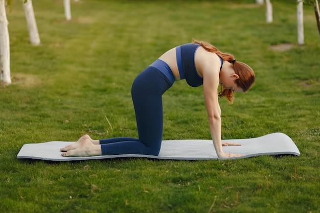 Linda garota fazendo yoga em um parque de verão Foto gratuita