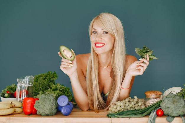 Linda garota fazer uma salada. loira desportiva em uma cozinha. mulher com abacate. Foto gratuita