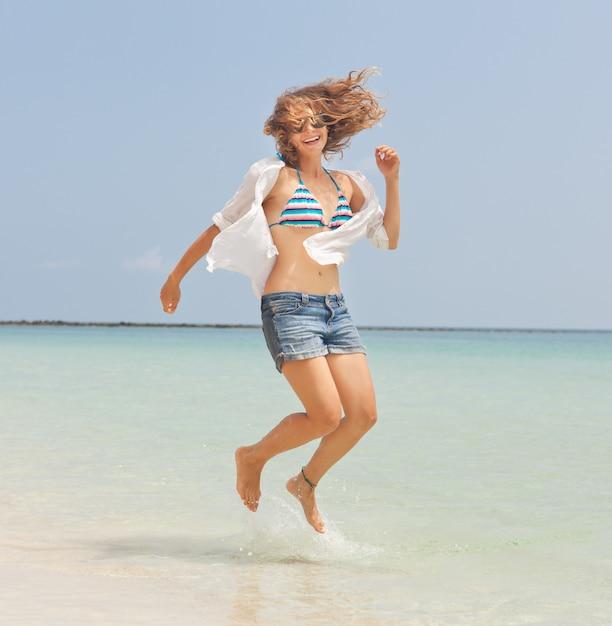 Linda garota feliz pulando na praia Foto Premium