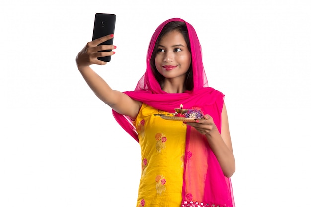 Linda garota feliz tomando selfie com pooja thali usando um telefone celular ou smartphone Foto Premium