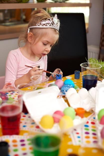 Linda garota focada em seus ovos de páscoa artesanais Foto gratuita
