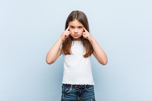 Linda garota focada em uma tarefa, mantendo-o dedos apontando a cabeça. Foto Premium