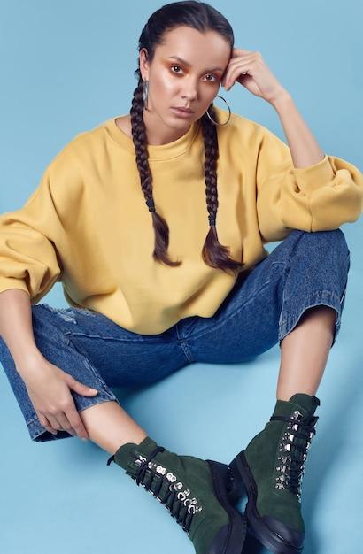 Linda garota hispânica encantadora em jeans e casaco com capuz amarelo Foto Premium