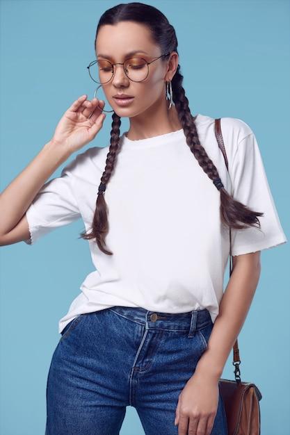 Linda garota hispânica encantadora em t-shirt branca, calça jeans e óculos Foto Premium