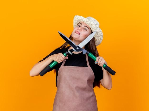 Linda garota jardineira alegre usando uniforme e chapéu de jardinagem segurando uma tesoura e mostrando a língua Foto gratuita