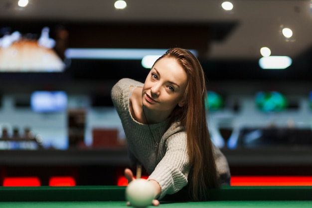 Linda garota joga bilhar em um bar Foto Premium