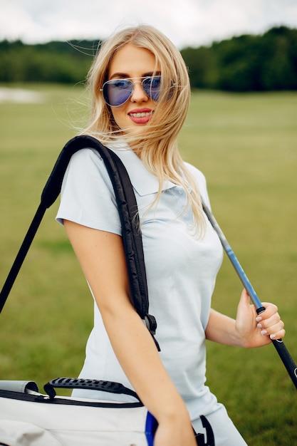 Linda garota jogando golfe em um campo de golfe Foto gratuita