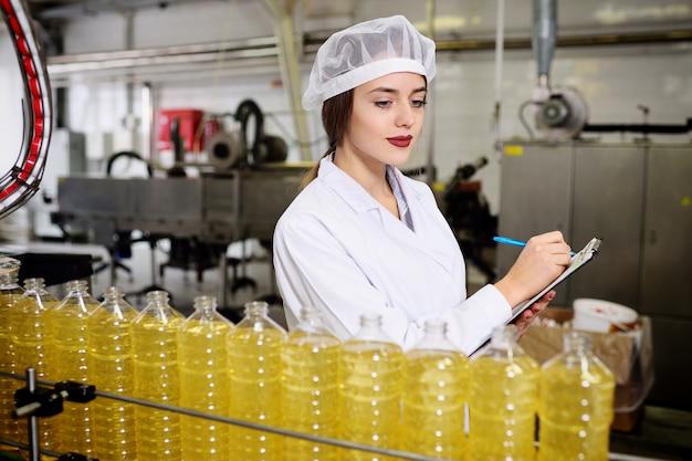 Linda garota jovem com uma garrafa de girassol ou azeite Foto Premium