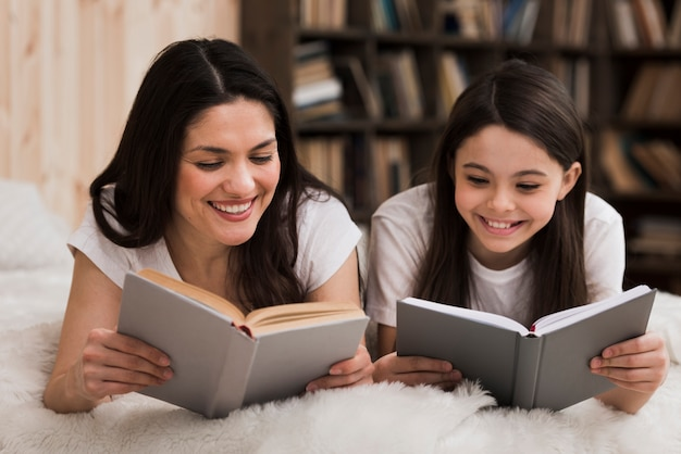 Linda garota jovem e mulher lendo livros Foto gratuita