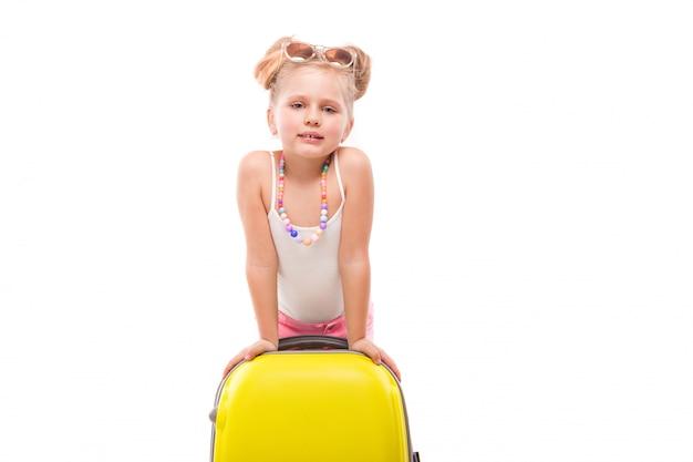 Linda garota jovem na camisa branca, calção rosa e óculos de sol fica perto de mala amarela Foto Premium