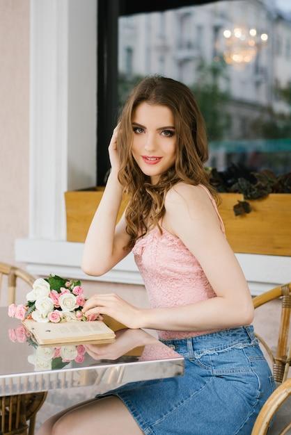 Linda garota jovem sentado em uma mesa em um café de rua de verão, segurando um livro nas mãos dela e sorrindo Foto Premium