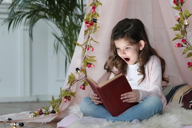 Linda garota lendo um livro sobre decoração fofa Foto gratuita