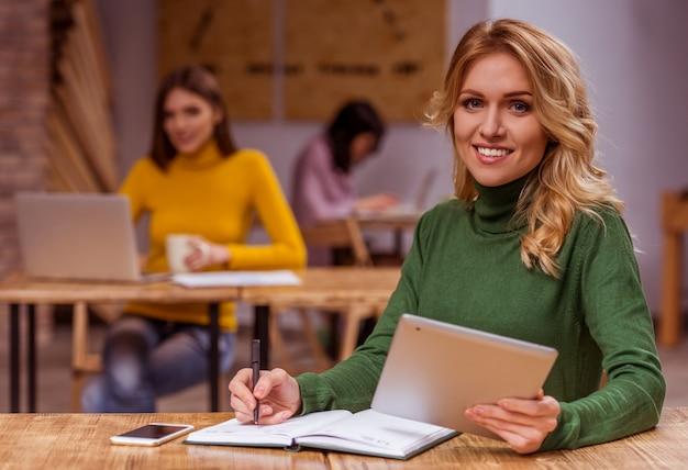 Linda garota loira em roupas casuais, usando o tablet. Foto Premium
