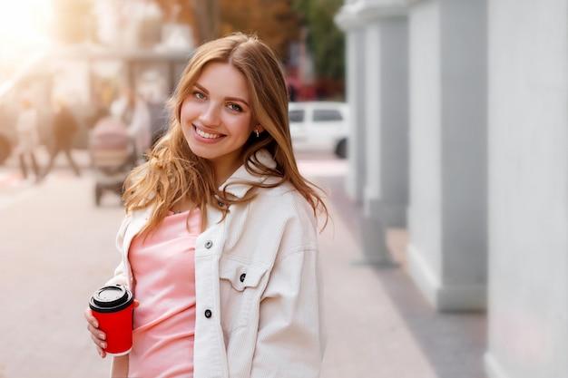 Linda garota loira está andando na cidade com uma xícara de café e sorrindo Foto Premium