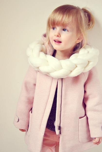 Linda garota loira feliz gengibre cachecol de malha gigante com estrela natal conceito decoração de ano novo Foto Premium